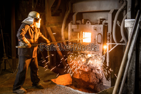 steel worker in protective clothing raking