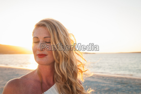 blond woman with eyes closed on