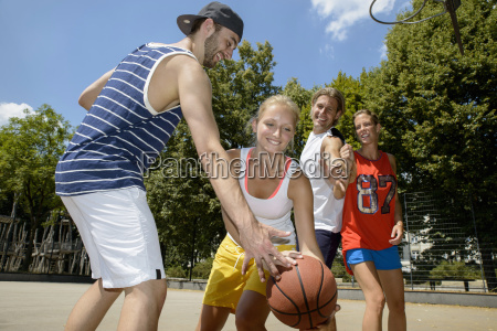 group of friends playing basketball in