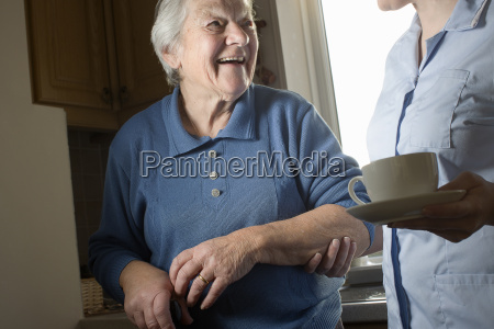 personal care assistant carrying cup of