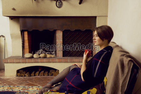 young woman sitting on sofa wrapped
