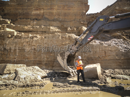 worker standing next to excavator inspecting