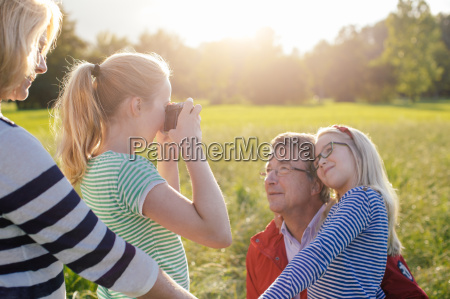 girl photographing grandfather and sister