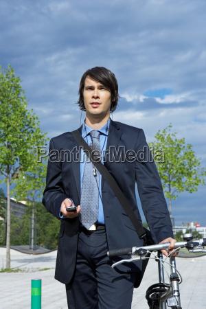 businessman in park walking his bike