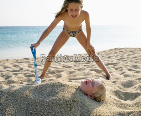 young girl burying young boy in