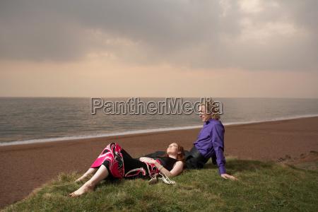couple sitting next to a beach