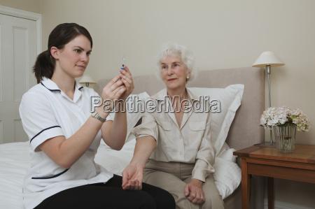 nurse preparing injection for woman