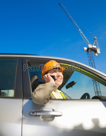woman using phone at building site