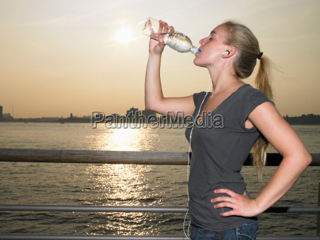 woman with mp3 player drinking water