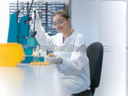 female worker sat at workbench using