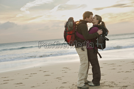 backpacking couple kissing at beach