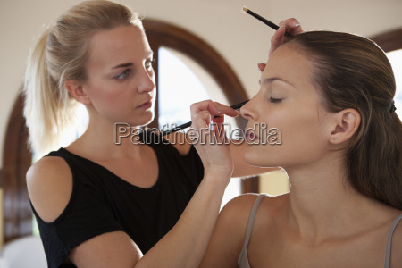 makeup artist applying eyeliner to model