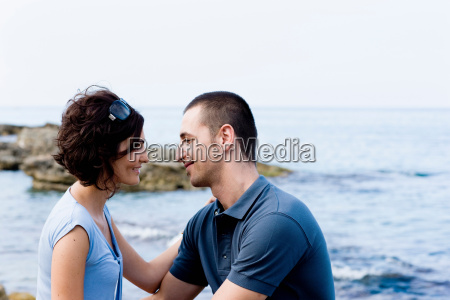 couple, sitting, together, on, waterfront - 18254268