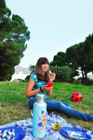 teenage girl eating at picnic
