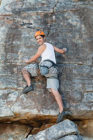 climber scaling steep rock face