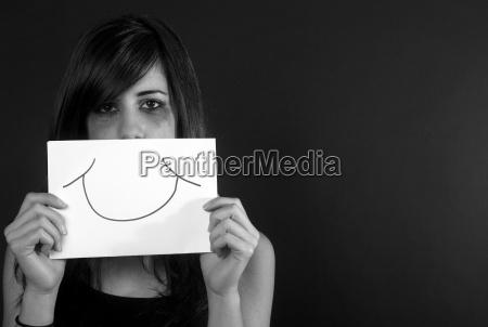 crying teenage girl holding fake smile