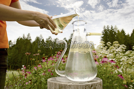 worker pouring chemicals in field
