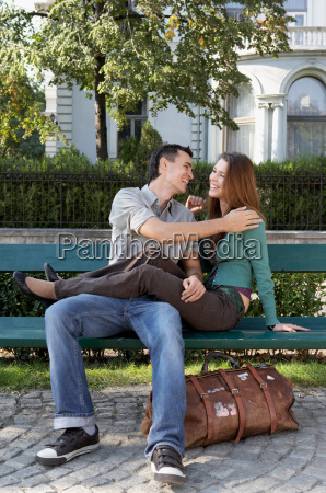couple sitting on a bench laughing