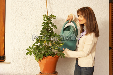 woman watering pot plant smiling