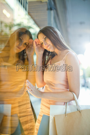 young woman with shopping bags looking