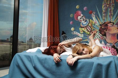 two sleepy young women lying on