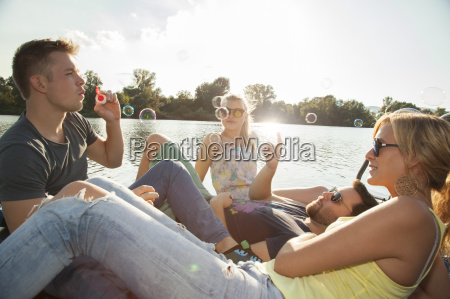 four young adult friends blowing bubbles