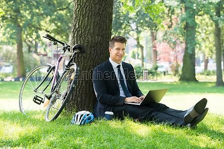 businessman using laptop in park