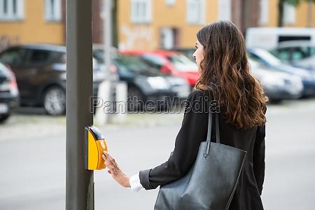 businesswoman pressing yellow crosswalk button