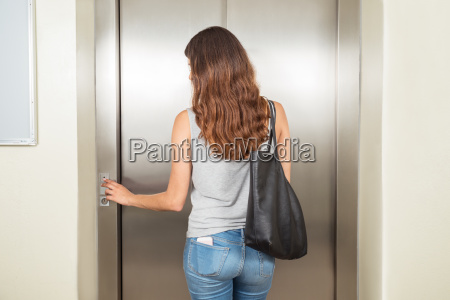woman with handbag using elevator