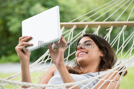 woman lying on hammock looking at