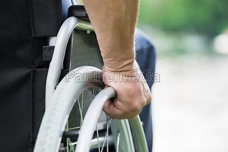 disabled man pushing wheel of wheelchair