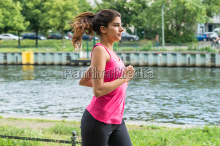 female athlete running near the pool