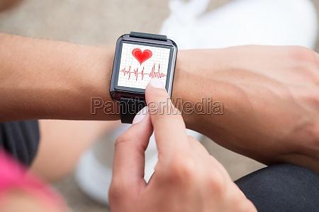 human hand wearing smart watch showing