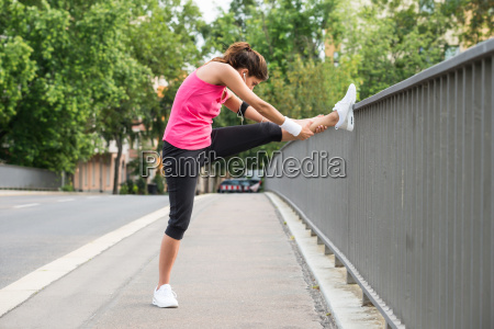 young woman stretching her legs