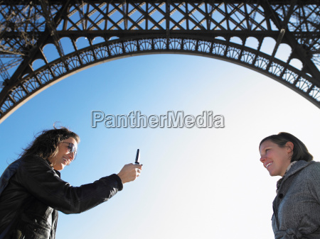 women taking picture under eiffel tower