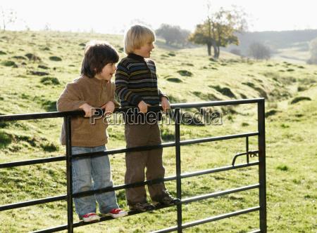 two boys swinging on gate in