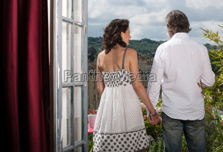 couple holding hands on balcony