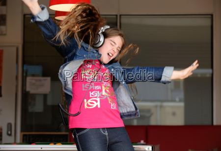 girl wearing headphones jumping