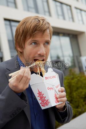 man eating chinese take away for