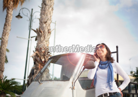 woman on phone by small van