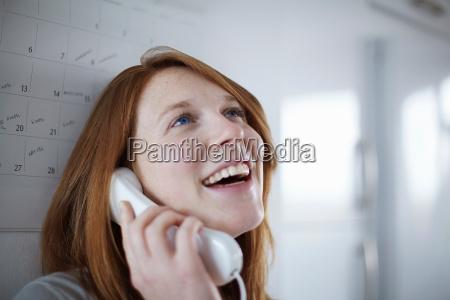 girl on telephone leaning on calendar