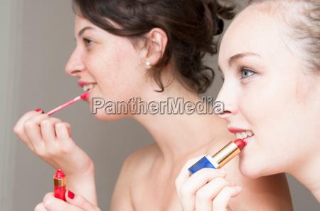 teenage girls applying makeup