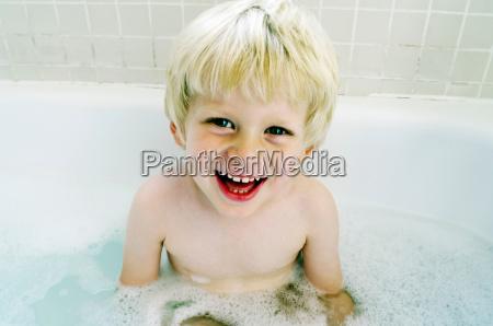 smiling boy sitting in bath