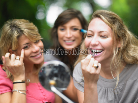 women applying makeup in car mirror