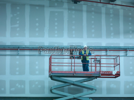 portrait of workman on scissor lift