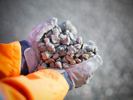 gloved hands holding crushed stones in