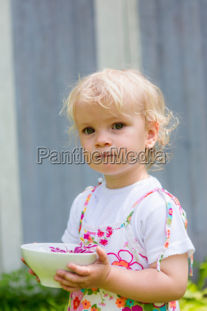 girl holding flower in bowl outdoors