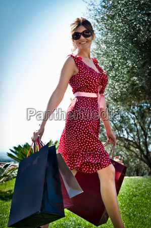 woman carrying shopping bags in grass