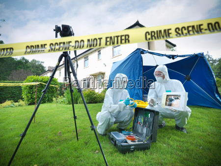 forensic scientists with toolkit behind police