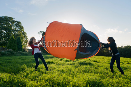 teenage girls pitching tent in field